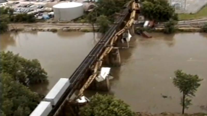 FILE - A freight train with attached semi-trailer cars dangles from a bridge over the Iowa...