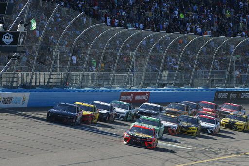 Martin Truex Jr. (19) leads the field through Turn 4 on a restart during the NASCAR Cup Series auto race at Phoenix Raceway, Sunday, March 8, 2020, in Avondale, Ariz. (AP Photo/Ralph Freso)