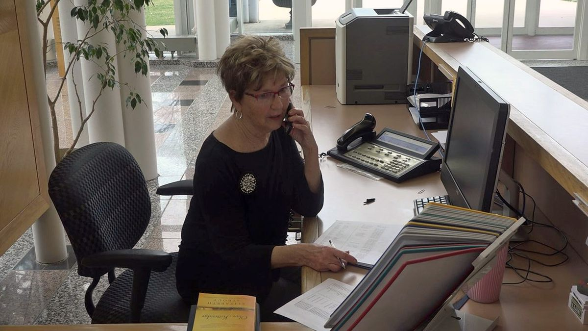 Clarke University welcome desk receptionist Mary Ellen Herbst makes phone calls to students to check in on them amid the COVID-19 outbreak that forced students from the Dubuque campus. Photo Date: Tuesday, March 31, 2020. (Maggie Wedlake/KCRG)