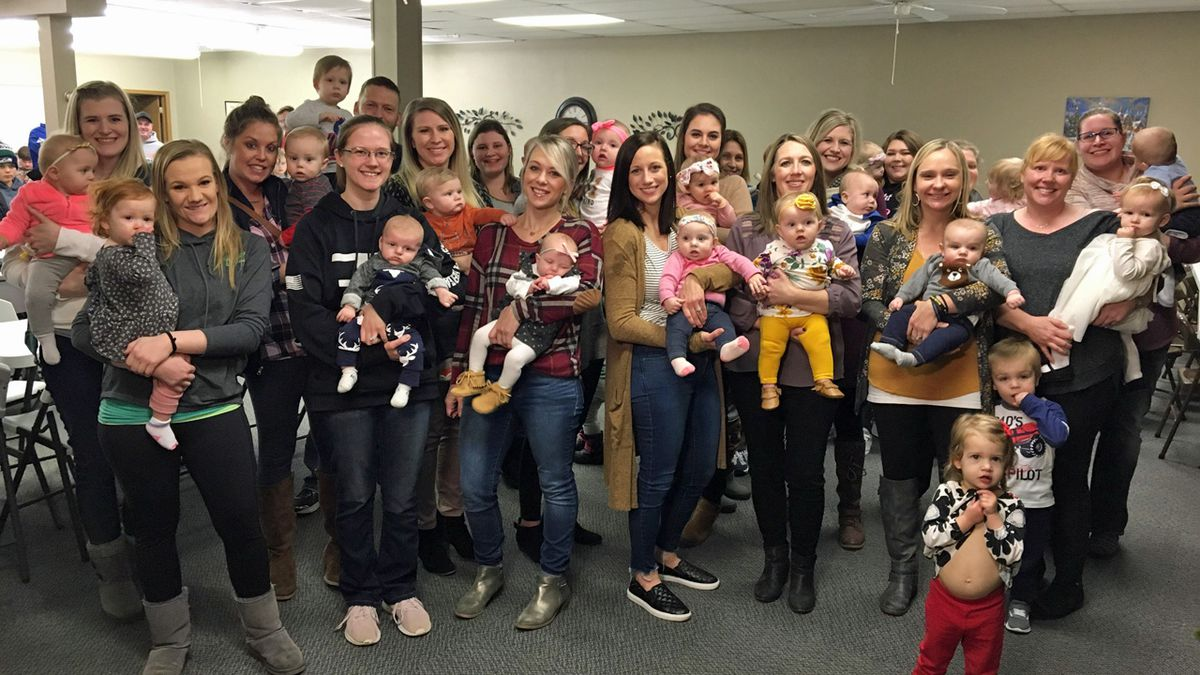 Families in Saint Lucas hold their children at a gathering on Monday, Jan. 6, 2020 (Allison Wong/KCRG)