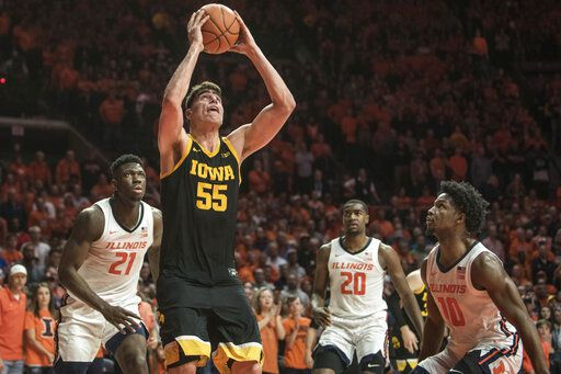 Iowa's Luka Garza (55) shoots as Illinois' Kofi Cockburn (21), Da'Monte Williams (20), and Andres Feliz (10) defend in the second half of an NCAA college basketball game Sunday, March 8, 2020, in Champaign, Ill. (AP Photo/Holly Hart)