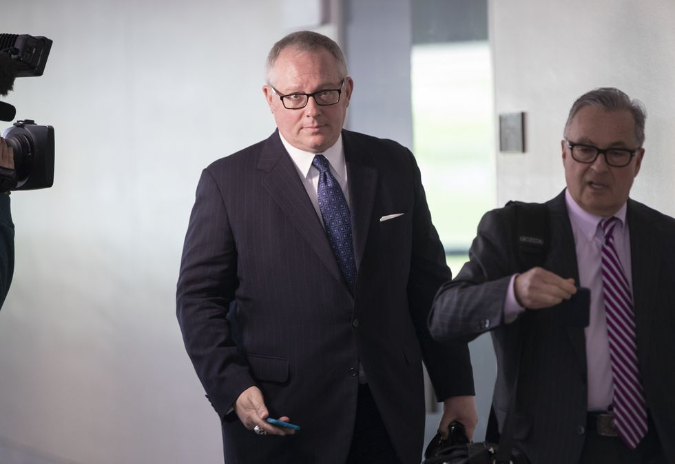 In this May 1, 2018, file photo, Former Donald Trump campaign official Michael Caputo, left, joined by his attorney Dennis C. Vacco, leaves after being interviewed by Senate Intelligence Committee staff investigating Russian meddling in the 2016 presidential election, on Capitol Hill in Washington. Now a federal official in the Department of Health and Human Services, he's taking a leave of absence.