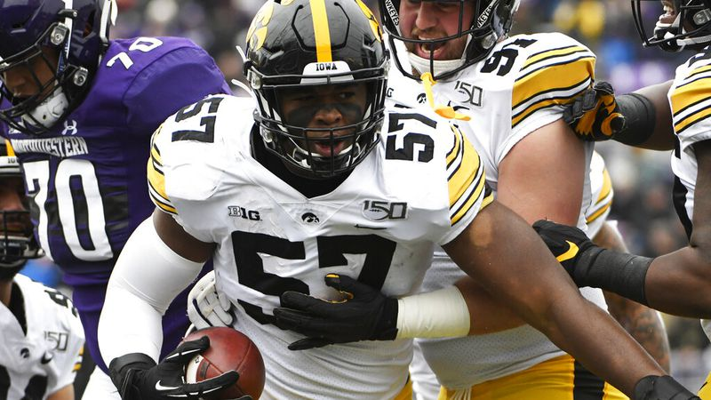 Iowa defensive end Chauncey Golston (57) reacts after intercepting a pass against Northwestern...