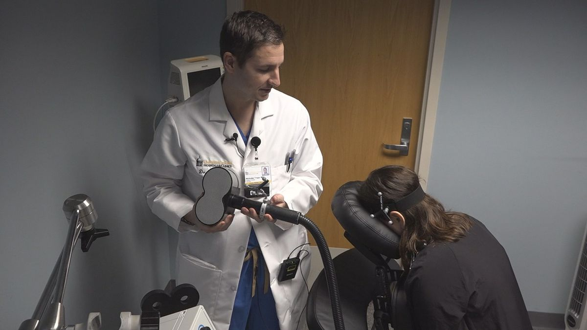 Dr. Nicholas Trapp, left, prepares to demonstrate transcranial magnetic stimulation at the...