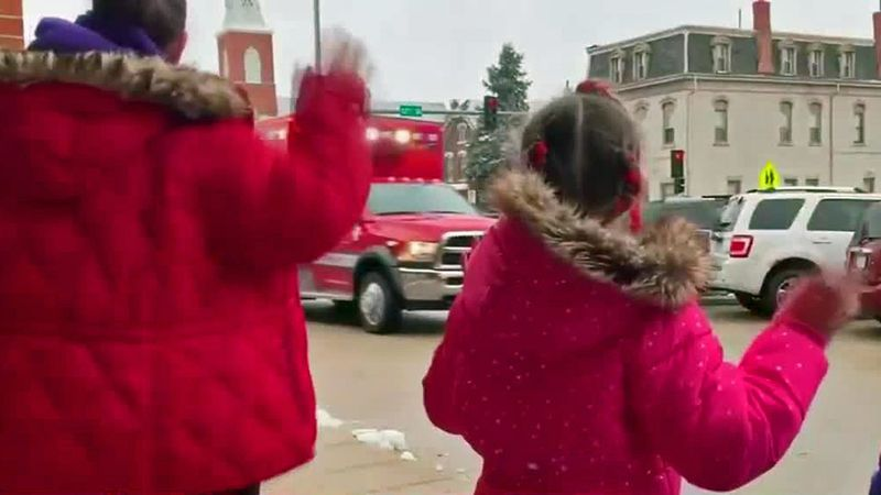The first-graders waved at police officers, fire fighters, and library, restaurant, and...