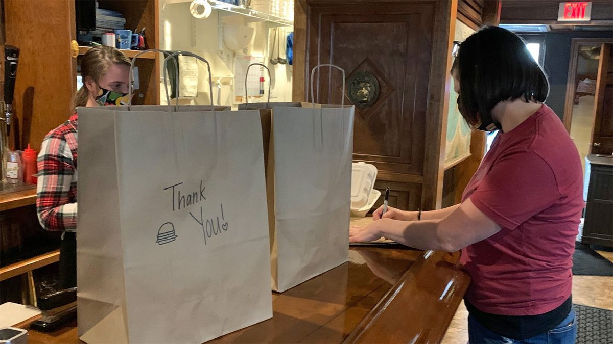 Christina Springman, right, writes notes on carry-out bags at The Map Room in Cedar Rapids on Wednesday, May 20, 2020. (Mary Green/KCRG)