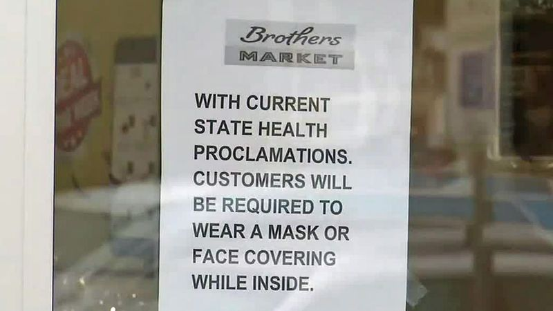 A sign on the door at Brothers Market in Lisbon, indicating that masks are required by patrons...