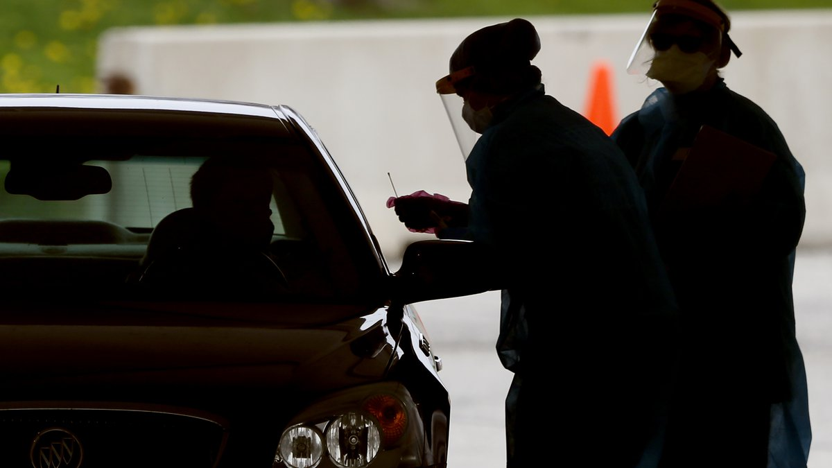 In this Friday, May 1, 2020, photo, medical workers test a local resident at a drive-thru...