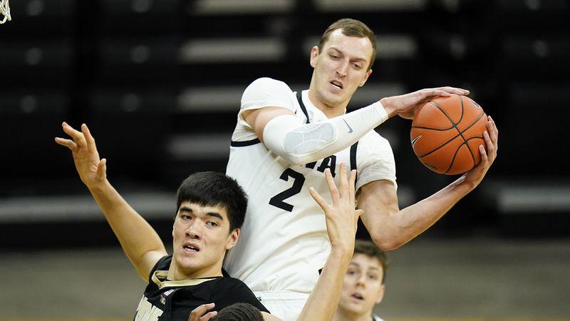 Iowa forward Jack Nunge (2) grabs a rebound over Purdue center Zach Edey, left, during the...