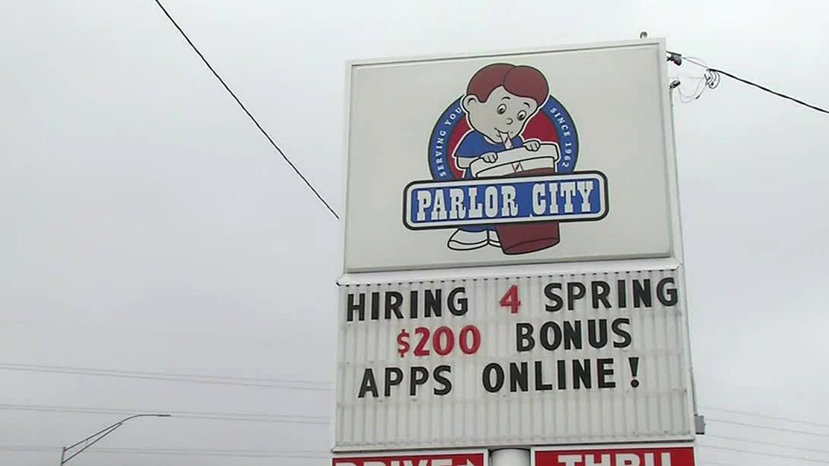 FILE - A sign at Parlor City Ice Cream in Cedar Rapids that offered $200 sign-on bonuses to get...