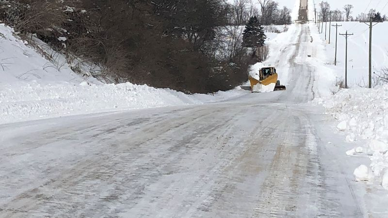 Crews clearing a road of drifting snow