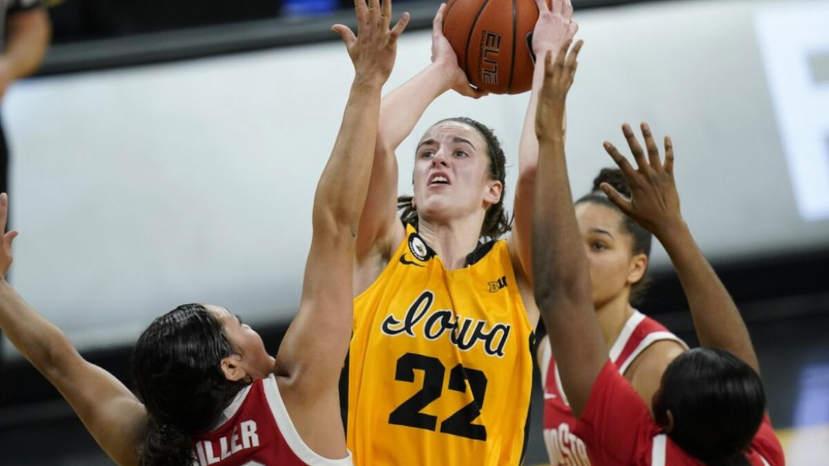 Iowa guard Caitlin Clark (22) drives to the basket between Ohio State guard Braxtin Miller (10)...