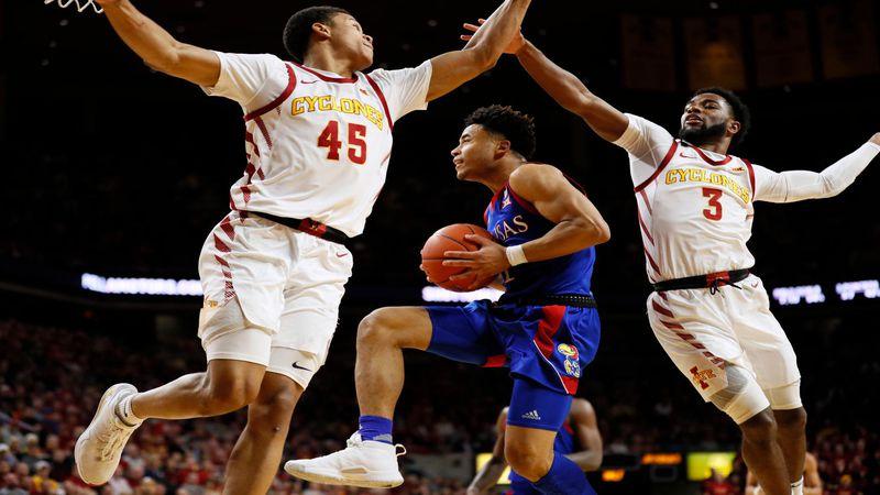Kansas guard Devon Dotson, center, drives to the basket between Iowa State's Rasir Bolton,...