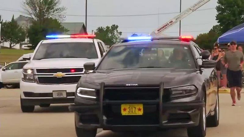 """Law enforcement vehicles and officers participate in Zechariah Cartledge's """"Running 4 Heroes""""..."""