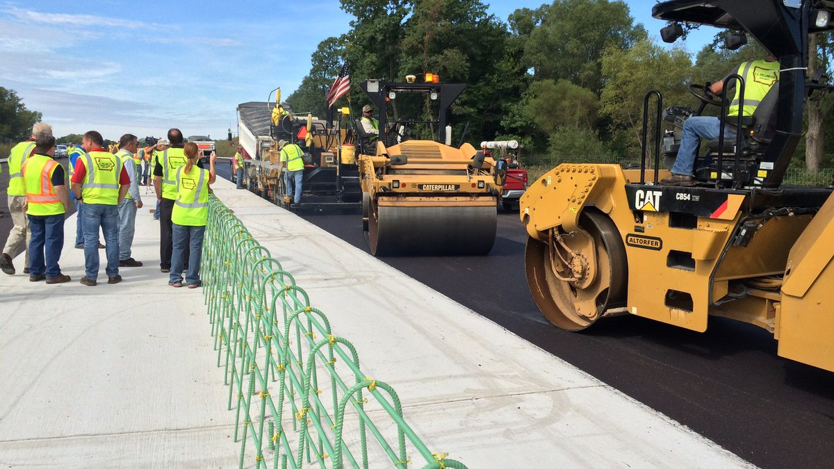 County engineers, contractors and others inspect asphalt work on the Highway 100 extension...