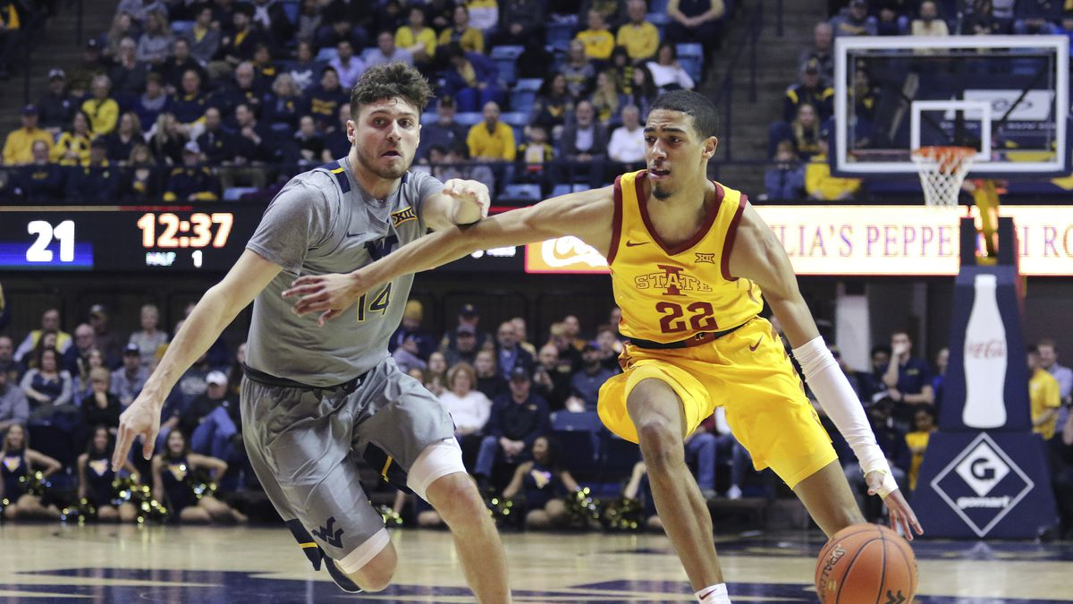 Iowa State guard Tyrese Haliburton (22) drives up court as he is defended by West Virginia guard Chase Harler (14) during the first half of an NCAA college basketball game Wednesday, Feb. 5, 2020, in Morgantown, W.Va. (AP Photo/Kathleen Batten)