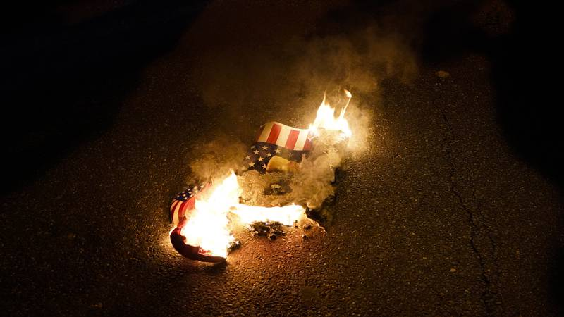 FILE - In this Nov. 14, 2020, file photo, a sign that counter-protesters lit on fire burns...
