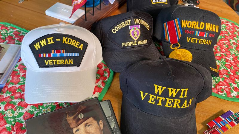 John Gualtier's collection of hats acknowledging his military service.
