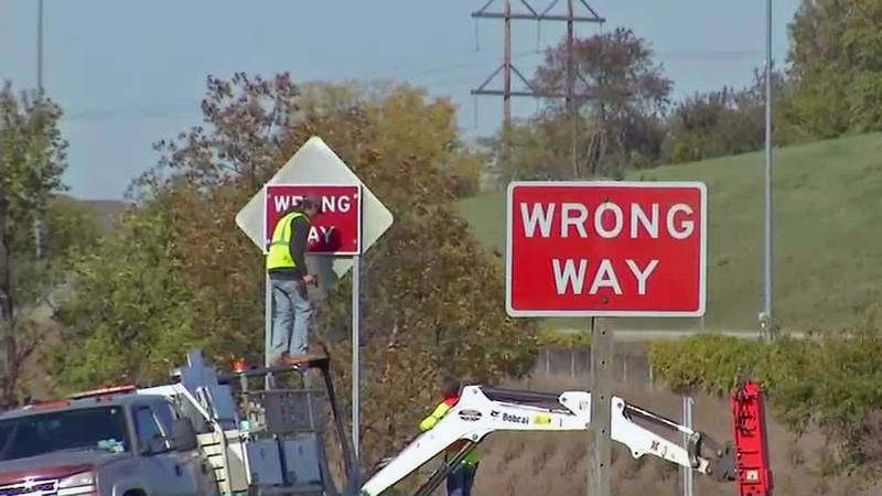 Iowa Department of Transportation workers install newer, larger wrong way signage in Cedar...