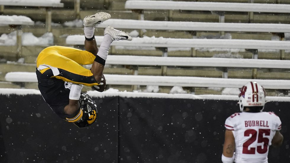 Iowa wide receiver Ihmir Smith-Marsette, left, flips in the end zone in front of Wisconsin...