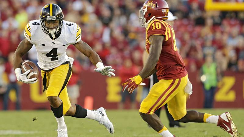 Iowa Hawkeyes wide receiver Tevaun Smith (4) tries to avoid Iowa State Cyclones defensive back...