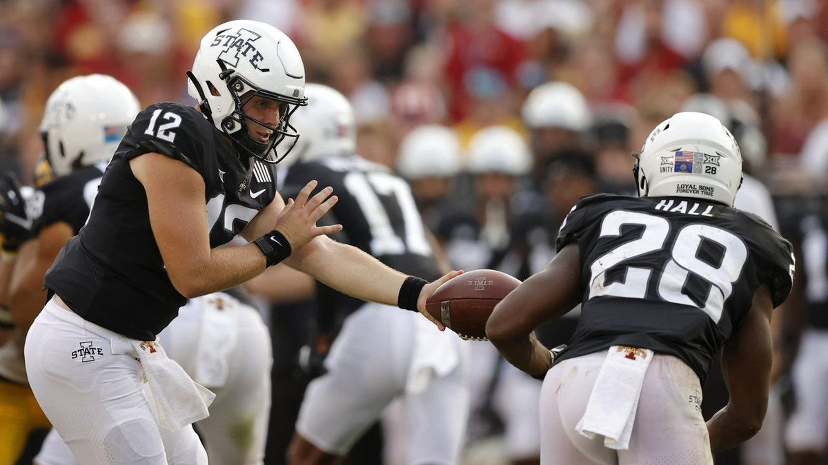 Iowa State quarterback Hunter Dekkers (12) hands off to running back Breece Hall (28) during...