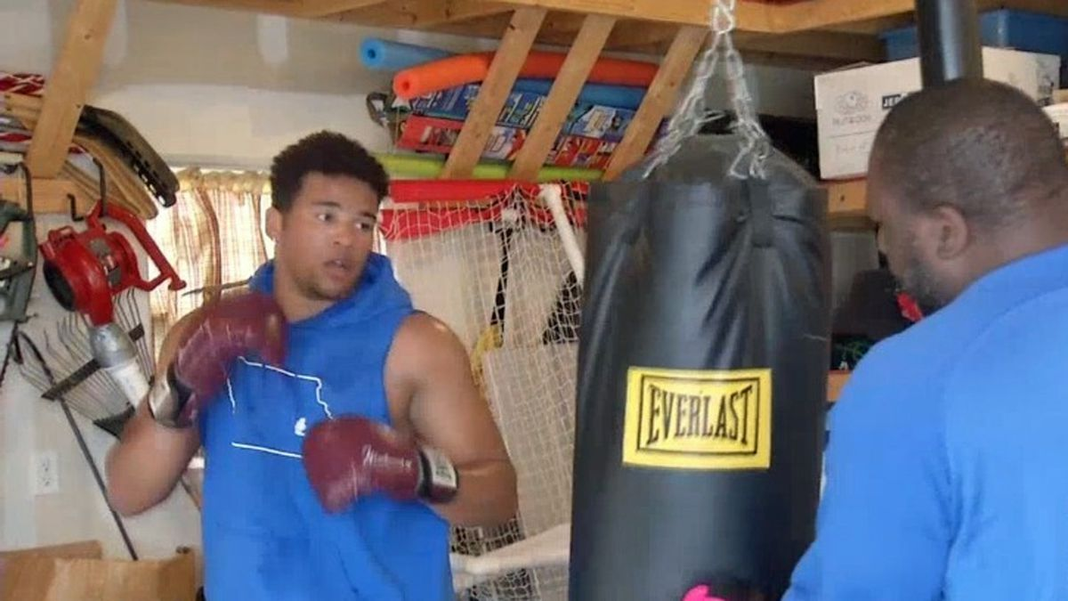 T.J. Bollers works a punching bag in the garage at his home in Tiffin with his dad, Trevor...
