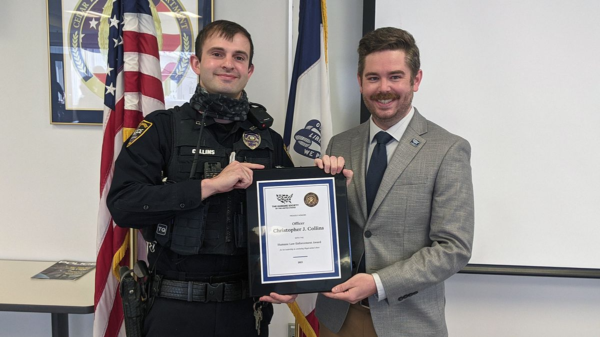 Christopher Collins, left, an officer with the Cedar Rapids Police Department, receives the...