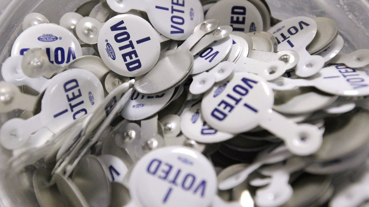 """""""I Voted"""" buttons lay in a bowl on the voting machine as voters case their ballots in..."""