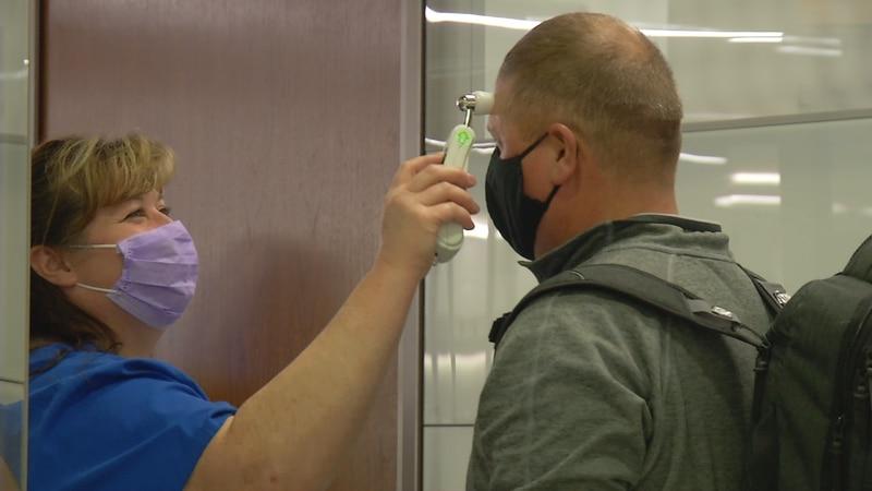 A Mercy Medical Center nurse takes a passengers temperature.